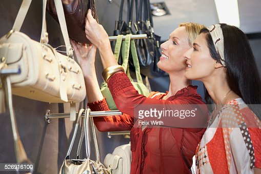 Women looking at purses : Stockfoto