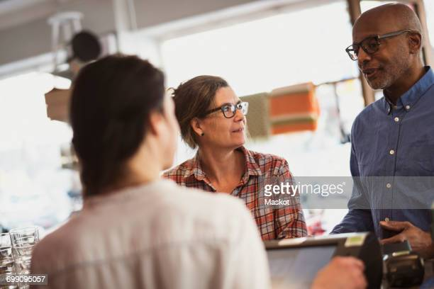 Women looking at senior male customer talking while standing by checkout counter in store