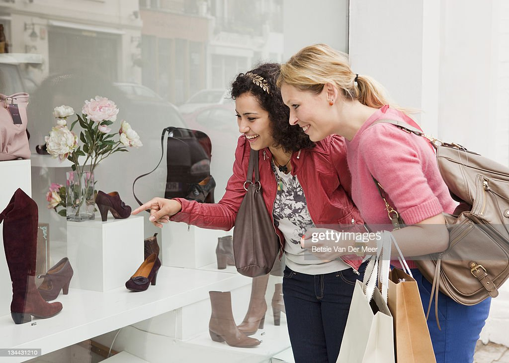 Women looking at shoes in shop window.