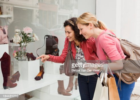 Women looking at shoes in shop window. : ストックフォト