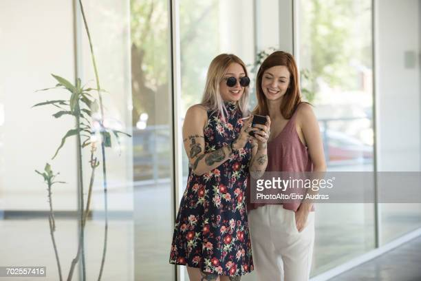 Women looking at smartphone together during cigarette break