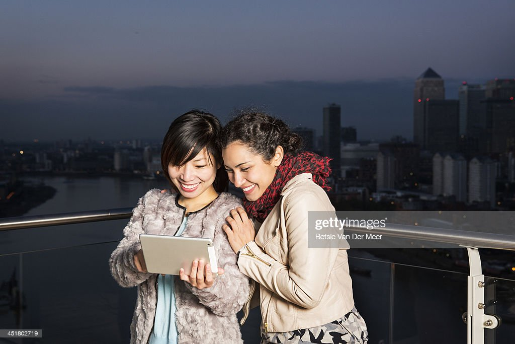 Women looking at wireless tablet at dusk. : Stock Photo