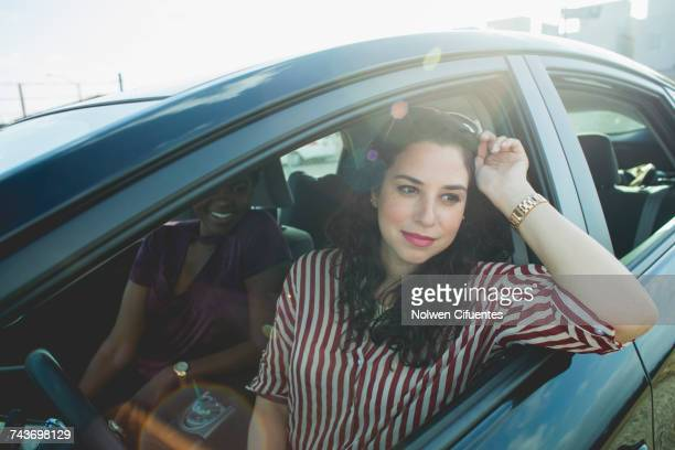 Women looking away while sitting with young female friend in car