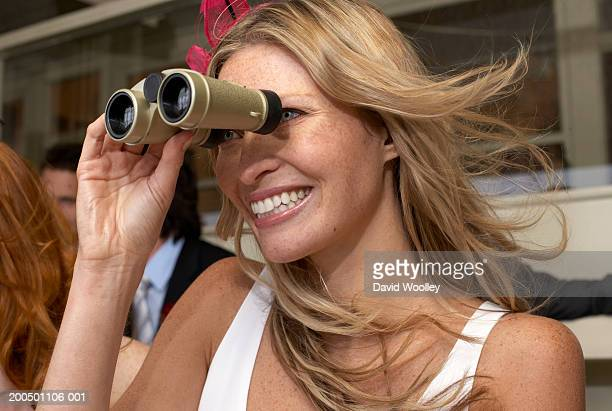 Women looking through binoculars at the races, smiling