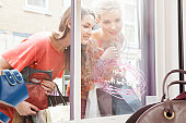women looking through shop window at bags.