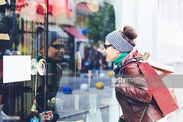 Femme regardant par la fenêtre de la boutique