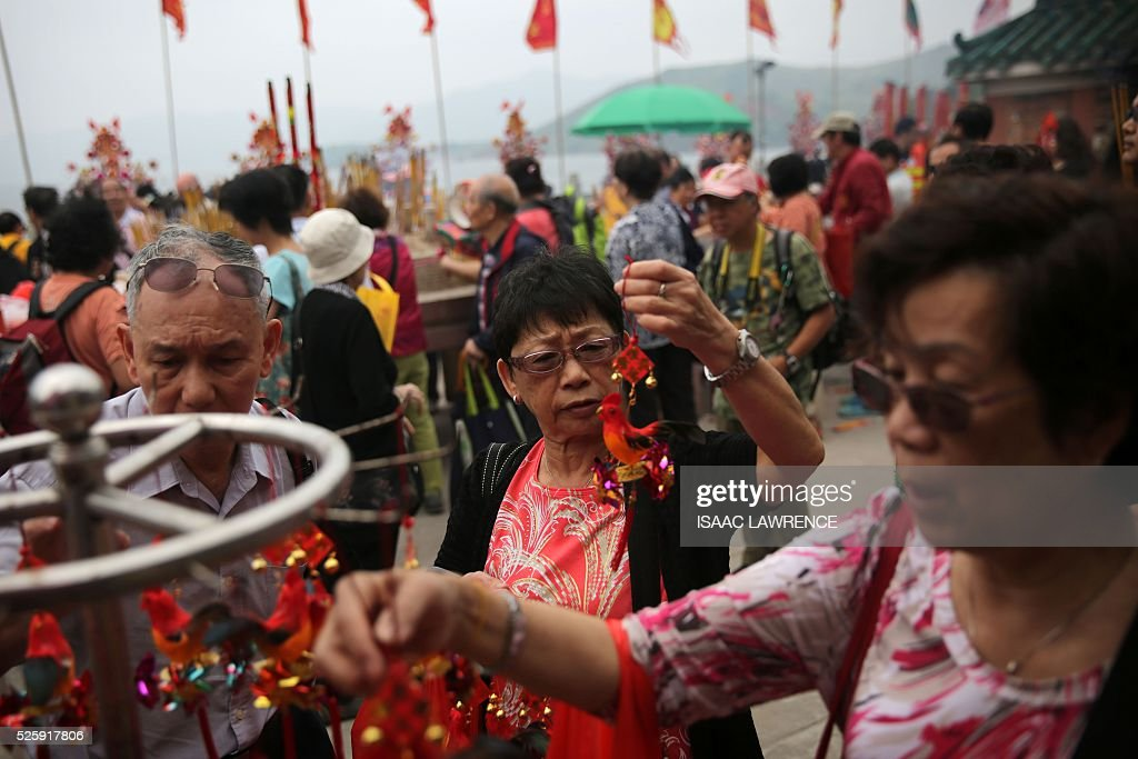 A women (C) looks at good luck charms during celebrations for the Tin Hau Festival outside the Joss House Bay Tin Hau temple in Hong Kong on April 29, 2016. Tin Hau is the Goddess of the Sea and patron saint of fishermen - On her birthday, locals flock to the more than 70 temples dedicated to her to pray for safety, security, fine weather and full fishing nets during the coming year. / AFP / ISAAC