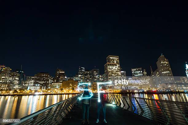 Women Making Light Painting While Standing On Footbridge At Night