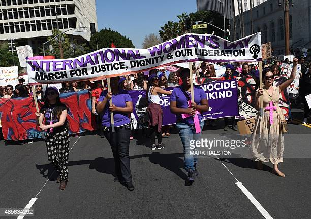 Women march behind a banners as they join other women's rights advocates in an International Women's Day march in downtown Los Angeles California on...