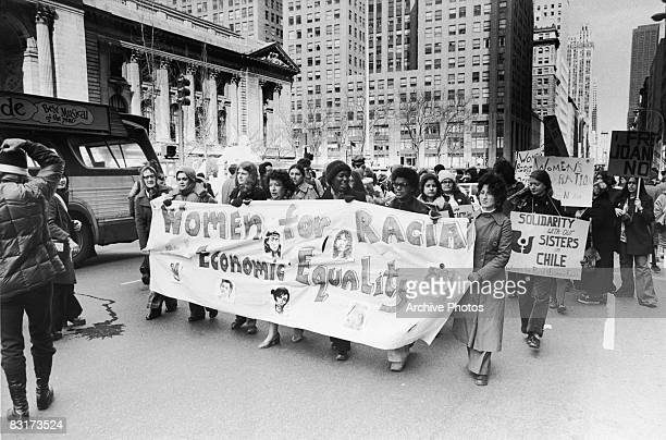 Women march holding a banner and signs during a demonstration for racial and economic equality on Fifth Avenue in New York City 1970s