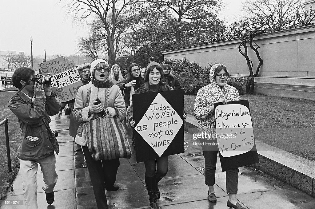 Women march in support of equal rights during the inaugural ceremonies for American President Nixon, Washington DC, mid-January 1969. The two signs in front read 'Judge women as people not as wives' and 'Distinguished ladies, when are you going to do your thing?'