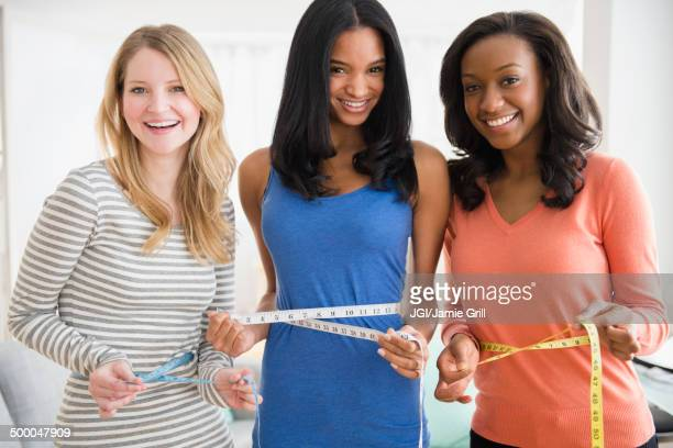 Women measuring their waistlines