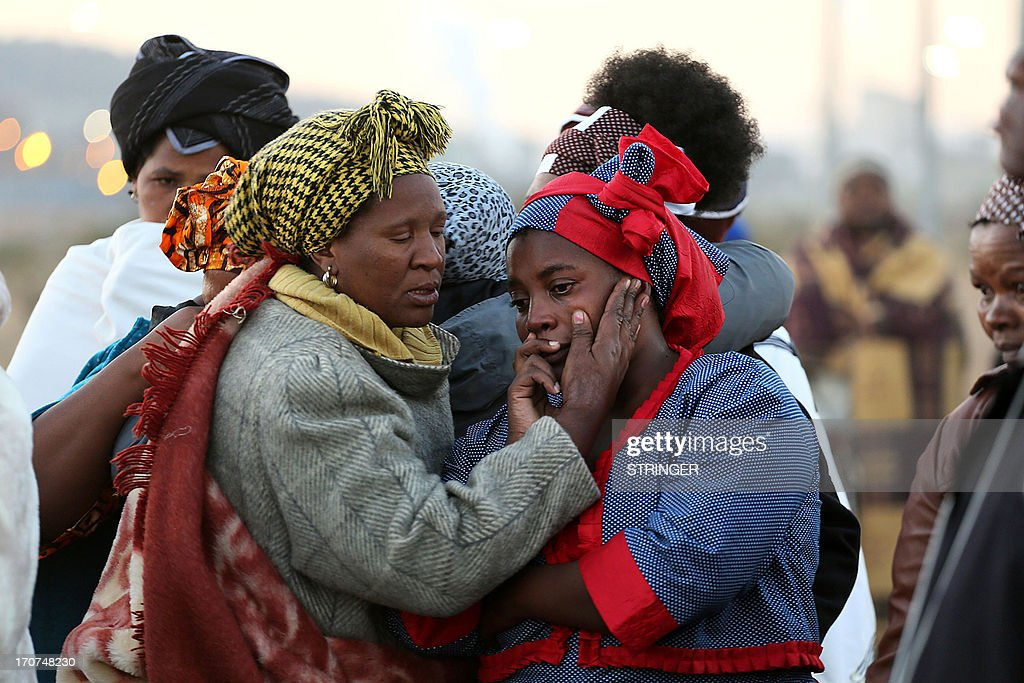 Women mourn as family members of the 34 people who died when police opened fire on strikers at the Lonmin platinum mine north west of Johannesburg on August 16, 2013 gather at the scene of the bloody shooting to cleanse the ground. Widows' songs of praise turned into frenzied wailing as they got off the bus. Each family got a sacrificial animal to slaughter as part of the cleansing ritual.