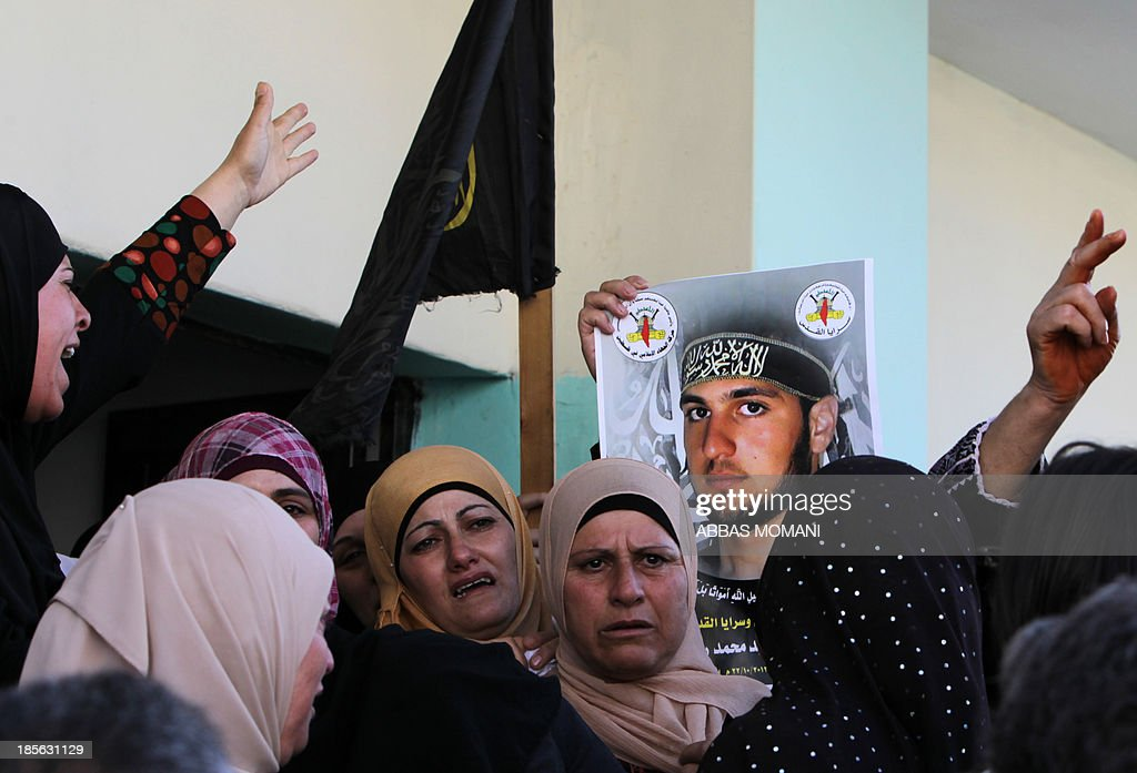 Women mourn during the funeral procession of Palestinian Islamic jihad militant Mohammed Assi (on the poster) on October 23, 2013 in the West Bank village of Beit Likya, who was killed by Israeli troops during a gunfight in the village of Bilin near Ramallah the previous day. Assi, 28, who was wanted for his alleged involvement in the 2012 bombing of a Tel Aviv bus, was killed when troops stormed an area between the West Bank villages of Bilin and Kufr Ne'meh, 10 kilometres (six miles) northwest of Ramallah officials said.