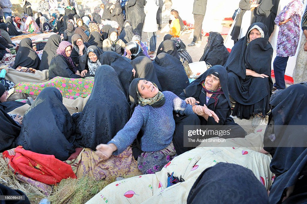 Women mourn surrounding the bodies of the earthquake victims on August 12, 2012 in Varzaqan, Iran. The two earthquake, within 11 minutes, jolted northwestern Iran on August 11, killed at least 300 people.