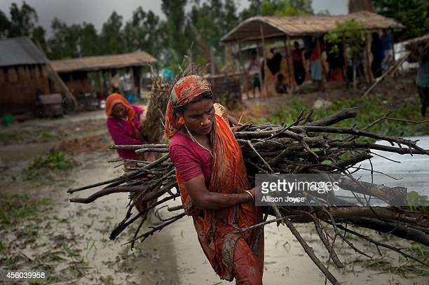 Women move possessions from their home that is threatened by river erosion September 22 2014 in the Kalashuna village in Gaibandha district of...