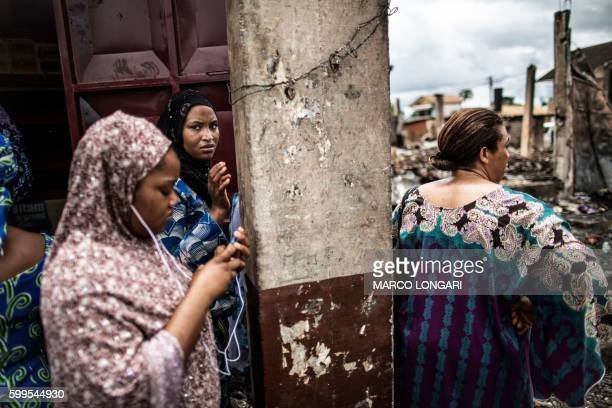 TOPSHOT Women observe a burned warehouse on September 5 2016 in Bitam northern Gabon near the border with Cameroon On September 1 post electoral...