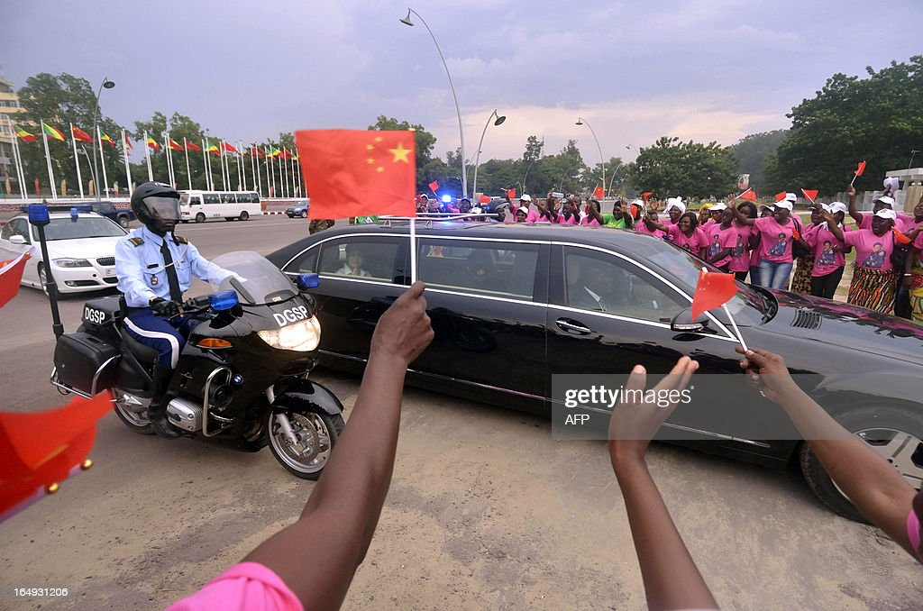 Women of the AMAS group ('Association Maman Antoinette Sassou') welcome Chinese President's wife, Peng Liyuan (at the limousine's backseat, L) and Congolese President's wife Antoinette Sassou Nguesso (unseen) upon their arrival by car on March 29, 2013 in front of the Foreign Affairs ministry in Brazzaville. China's new President Xi Jinping and his wife arrived in Brazzaville on March 29 on the final leg of a three-nation Africa tour that has underscored Beijing's growing presence in the resource-rich continent. Deals worth several billion dollars are due to be signed during Xi's two-day visit to Congo, the first by a Chinese president to the impoverished country of four million with significant oil resources. KANNAH
