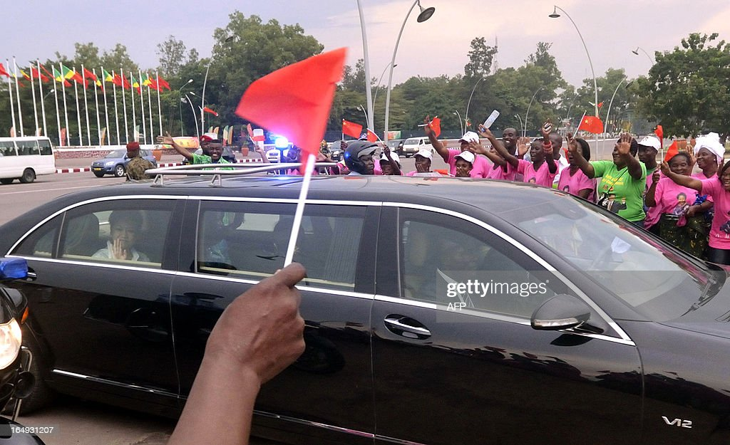 Women of the AMAS group ('Association Maman Antoinette Sassou') welcome Chinese President's wife, Peng Liyuan (at the limousine's backseat, L) and Congolese President's wife Antoinette Sassou Nguesso upon their arrival by car on March 29, 2013 in front of the Foreign Affairs ministry in Brazzaville. China's new President Xi Jinping and his wife arrived in Brazzaville on March 29 on the final leg of a three-nation Africa tour that has underscored Beijing's growing presence in the resource-rich continent. Deals worth several billion dollars are due to be signed during Xi's two-day visit to Congo, the first by a Chinese president to the impoverished country of four million with significant oil resources. KANNAH