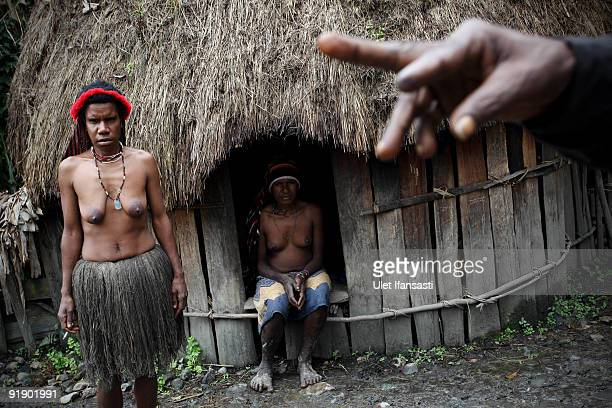 Women of the traditional Dani tribe from Lembah Baliem stand in front of their house on October 10 2009 in Wamena West Papua Indonesia The primitive...