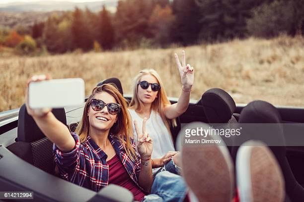 Women on a road trip taking selfie