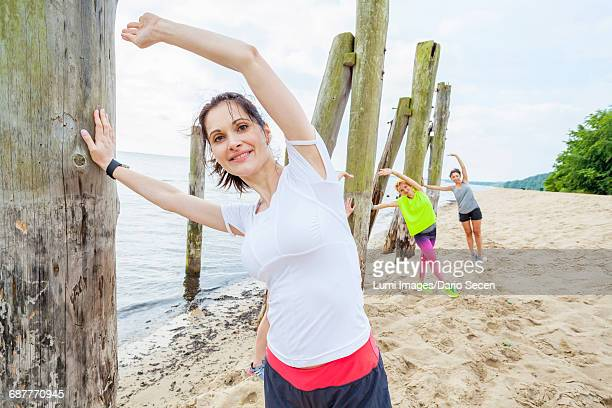 Women on beach doing stretching exercises