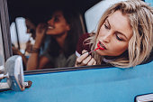 Three young woman going on a road trip. Female friends doing makeup in moving car.