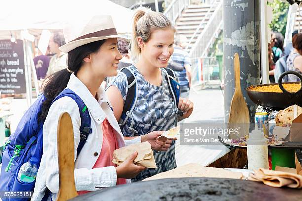 Women order food at food stall in market