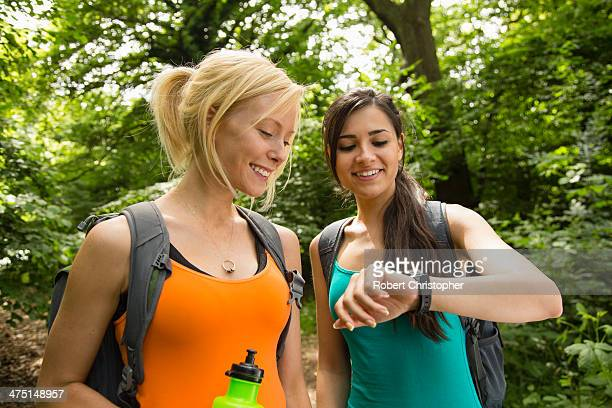 Women out walking in forest, checking the time