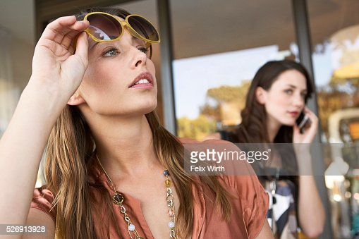 Women outside of boutique looking for taxi : Stock Photo