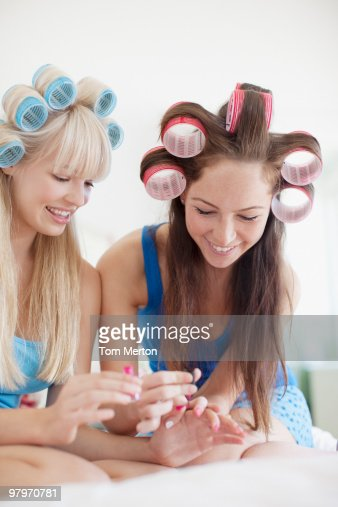Women painting fingernails with curlers in hair : Stock Photo