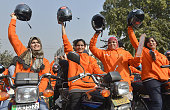 Women participants of Women on Wheels raise their helmets at the start of a rally launching the Women on Wheels campaign in Lahore on January 10 2016...