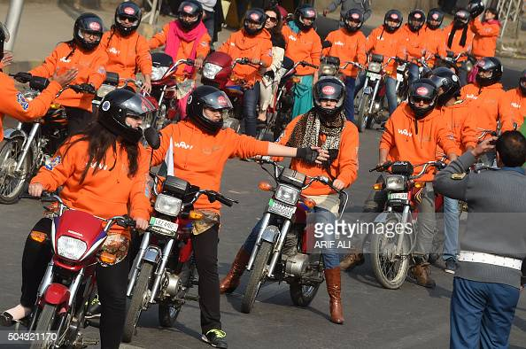 Women participants of Women on Wheels wait on their motorbikes prior to the start of a rally launching the Women on Wheels campaign in Lahore on...