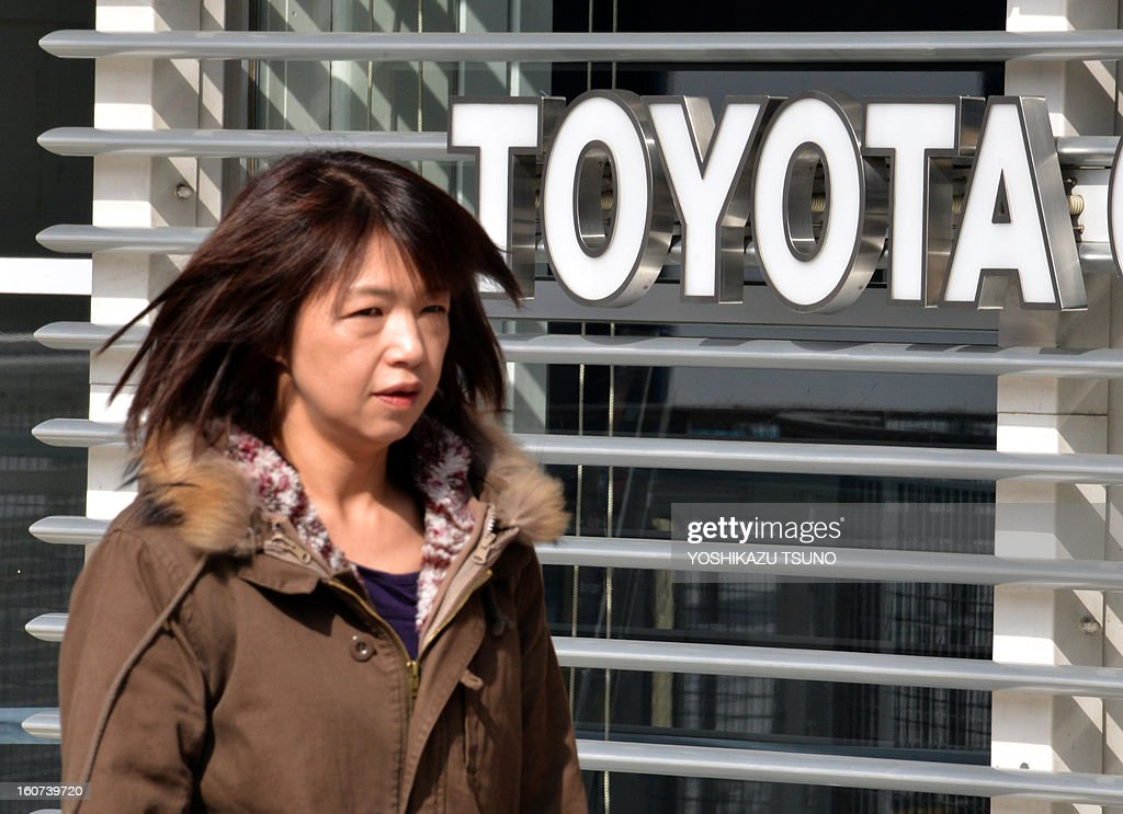 A women passes before a Toyota Motor sign at the company's showroom in Tokyo on February 5, 2013. Toyota said its net profit quadrupled for the nine months to December as the Japanese auto giant revised upward its full-year profit and sales forecast. AFP PHOTO / Yoshikazu TSUNO