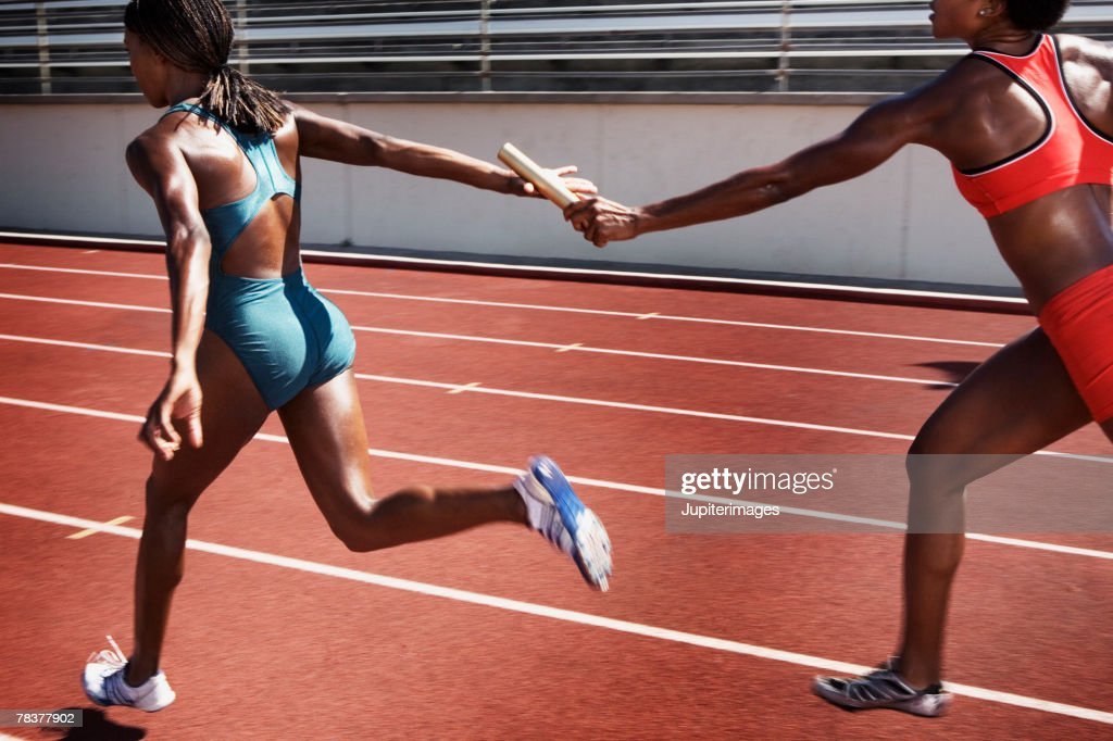 Women passing baton to each other during race : Stock Photo