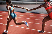 Women passing baton to each other during race