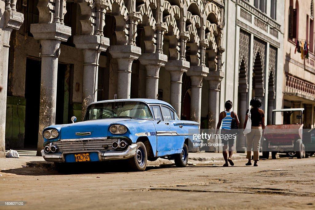 Women passing blue oldtimer car