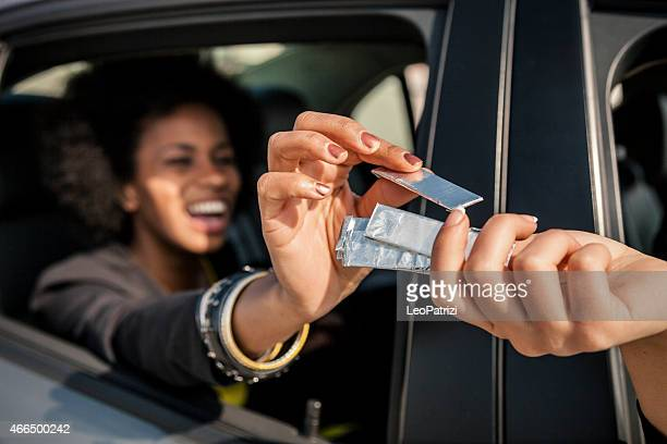 Women passing chewing gum out of the window car