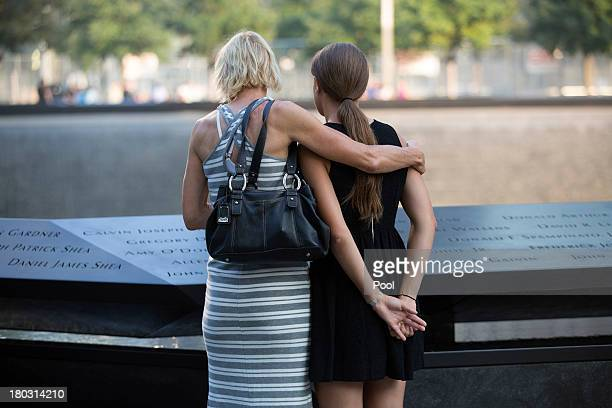 Women pause at the Cantor Fitzgerald section of the reflecting pool at the 9/11 Memorial before ceremonies for the 12th anniversary of the terrorist...