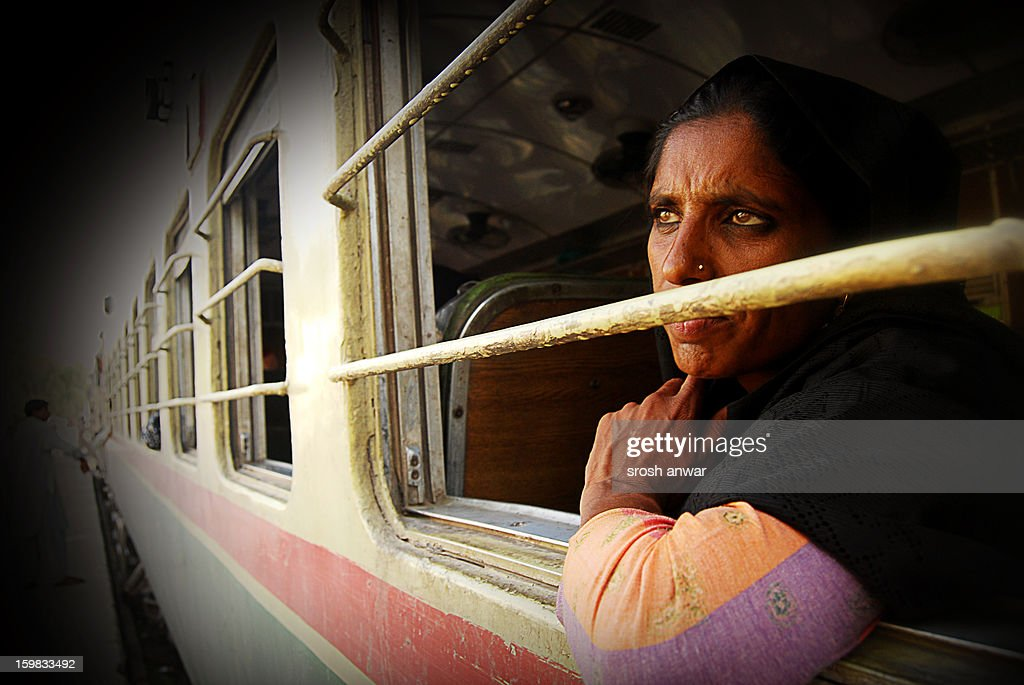CONTENT] A women peer out of window while the train stops at a railway station in Qasoor which is a small city, only two hours away from the historical city of Lahore, Punjab, Pakistan. This picture was taken some five years ago. In Pakistan, not only train is the best way to go around the country economically. The railway station is the center of activities showing its true culture and hustle bustle to an extent that many local movies have to have a scene on a train station. There are also songs about or on trains. But nowadays train has relegated to the choice of commute for the poor only because the people who can afford it, like to use airplanes.In Pakistan, railway was commonly referred to as the 'life line of the country', by aiding in large-scale movement of people and freight throughout Pakistan. The idea of a rail network was first thought of in 1847, with the possibility of Karachi becoming a major seaport. On May 13, 1861, the first railway line was opened to the public, between Karachi (city) and Kotri, with a total distance of 105 miles