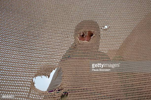 A women peers out from a torn curtain near her tent as the wind and dust blows making conditions in the massive tent city become more difficult May...