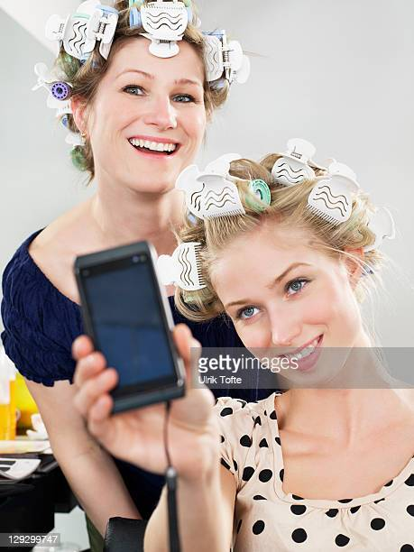 Women photographing themselves in salon
