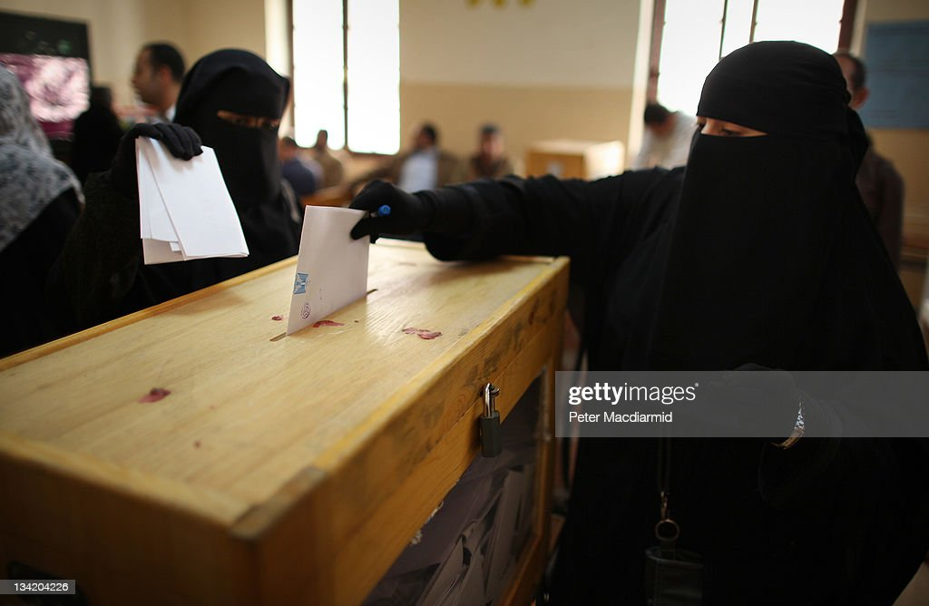 Women place their votes in a ballot box at a polling station in a girls school on November 28 2011 in Downtown Cairo Egypt Eleven months after the...