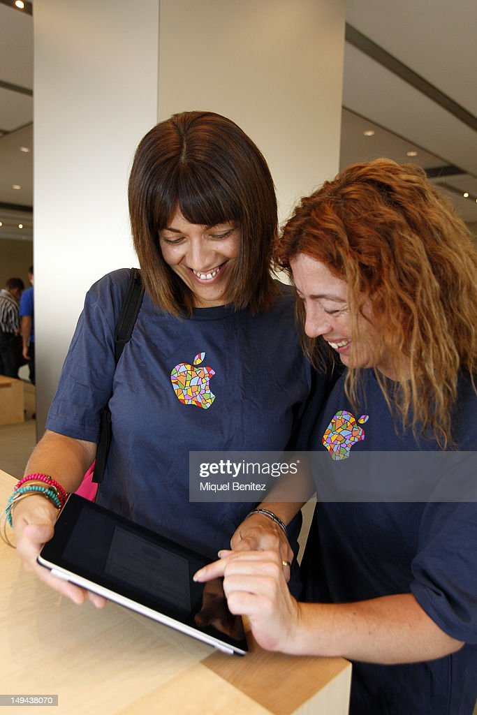 Women play with iPad as they attend the opening of Apple's New Barcelona Store in Passeig de Graciaon July 28, 2012 in Barcelona, Spain.