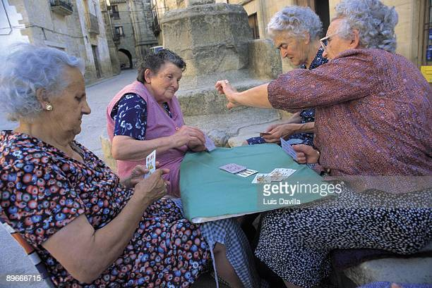 Women playing cards games Four old men playing cards game in a square of the Calaceite town Teruel province