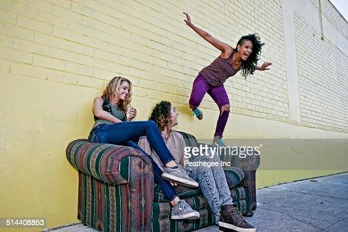 Women playing on sofa on city street