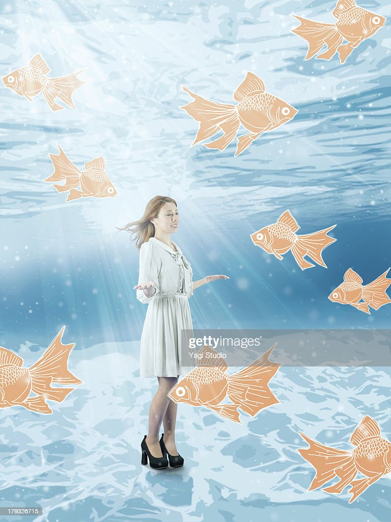 Women playing with fish in the water : Stock Photo