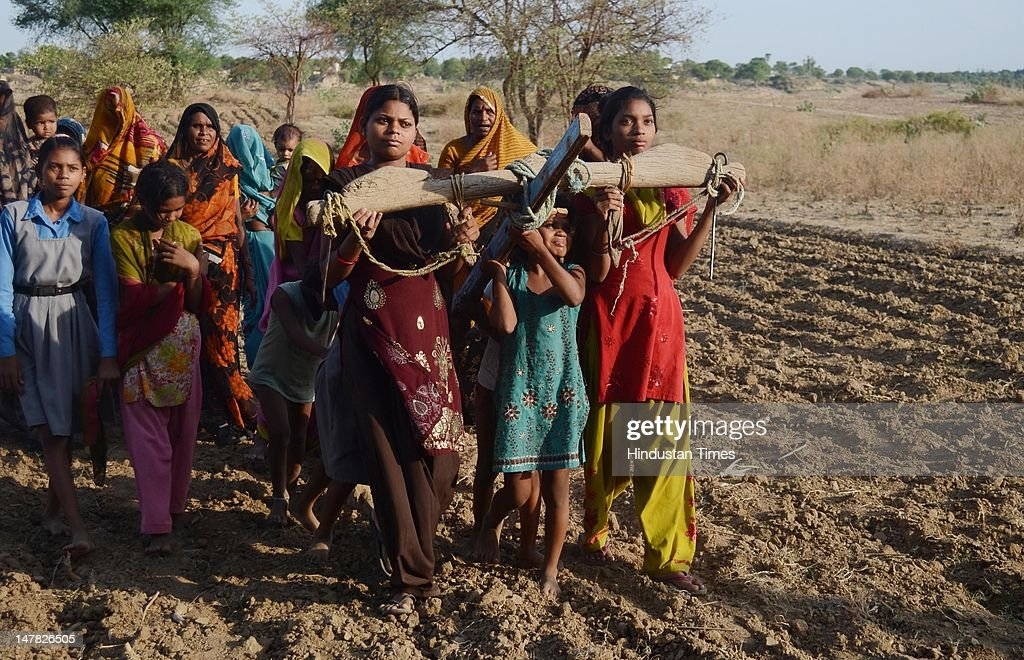 Women ploughing the dry fields as part of 'Har Padoury' Ritual to please the rain god at Benipur village on July 3, 2012 in Allahabad, India. Scant rainfall in the region of Eastern Uttar Pradesh has left farmers worried about their paddy crops which heavily depend on Monssons.