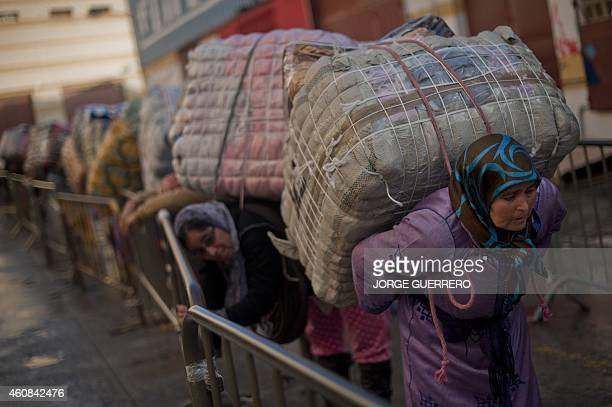 BAZINET Women porters queue carry bundles for transport across the El Tarajal boarder separating Morocco and Spain's North African enclave of Ceuta...