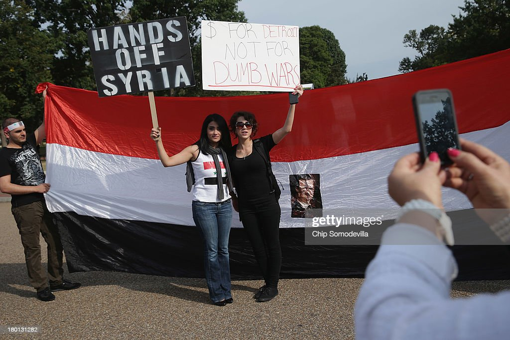 Women pose for a photograh with a banner bearing the image of Syrian President Bashar al-Assad during a demonstration in support of al-Assad and against a possible military attack on Syria by the United States outside the White House September 9, 2013 in Washington, DC. Organized by the Syrian American Forum (SAF), the demonstrators marched from the White House to the U.S. Capitol.